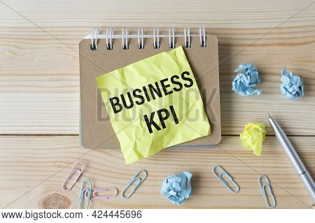 On The Business Card The Text Of Business Kpi, Next To The Pen, In The Background Of The Book And Di