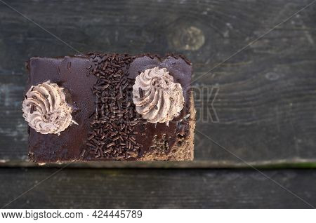 Three Chocolate Pastry Over Dark Wooden Background. Topped With Cream. Outdoors Shot