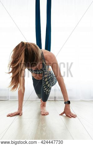 Woman Doing Anti-gravity Aero Yoga In A Room With Air Hammocks, Doing Warm-up And Stretching Before