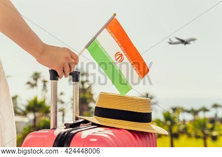 Woman With Pink Suitcase, Hat And Iran Flag Standing On Passengers Ladder And Getting Out Of Airplan