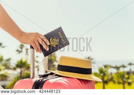 Woman With Pink Suitcase And Amerian Passport Standing On Passengers Ladder Of Airplane Opposite Sea