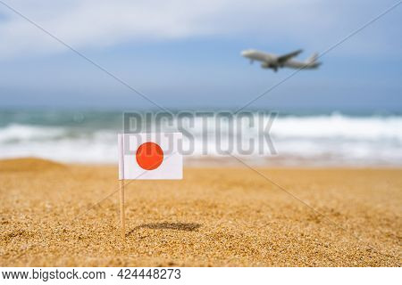 Flag Of Japan In The Form Of A Toothpick In The Sand Of Beach Opposite Sea Wave With Landing Airplan