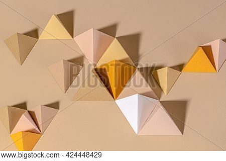 3D pyramid paper craft on a beige background
