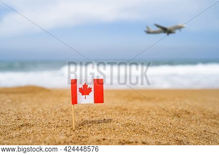 Flag Of Canada In The Form Of A Toothpick In The Sand Of Beach Opposite Sea Wave With Landing Airpla