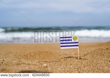 Flag Of Uruguay In The Form Of A Toothpick In The Sand Of Beach Opposite Sea Wave. Travel Concept
