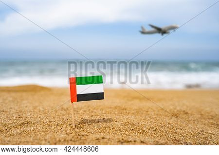 Flag Of United Arab Emirates In The Form Of A Toothpick In The Sand Of Beach Opposite Sea Wave With