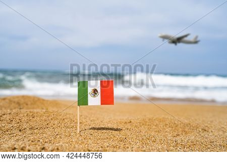 Flag Of Mexico In The Form Of A Toothpick In The Sand Of Beach Opposite Sea Wave With Landing Airpla