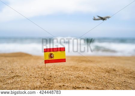 Flag Of Spain In The Form Of A Toothpick In The Sand Of Beach Opposite Sea Wave With Landing Airplan