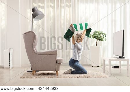 Excited female football fan kneeling in front of tv and cheering with a scarf