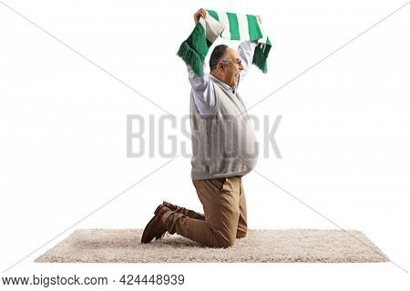 Exctied mature man kneeling on a carpet and cheering with a scarf isolated on white background