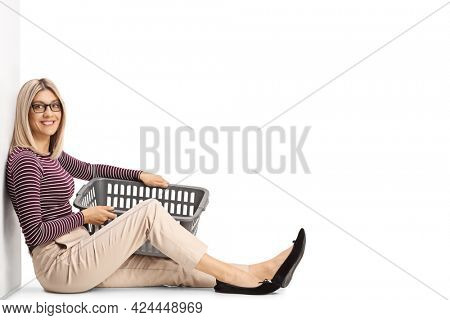 Young woman sitting, leaning on a wall and holding a laundry basket isolated on white background