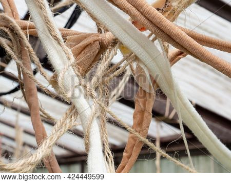 Many Suspended Chaotically Intertwined Ropes And Ribbons Of Cloth Tied Into Knots