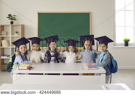 Portrait Of A Group Of Graduates Of Kindergarten Or Junior Class In Bachelor Hat Or Mortarboard.
