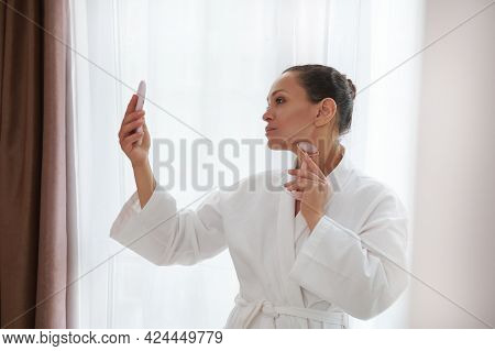 Side Portrait Of A Pretty Woman In Bathrobe Massaging Her Neck With A Jade Stone Roller Massager And