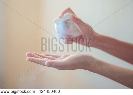 Hands Applying Alcohol Spray Or Anti Bacteria Spray. Personal Hygiene Concept. Cleaning Hands With S