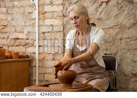 Senior Woman Potter Sculpts A Clay Pot. The Sculptor Works With Clay On A Potters Wheel And At A Tab