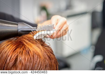Closeup Of Masters Hand With Blow-drying And Hairbrush Blowing Female Red Hair In A Salon