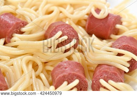 Close-up image of hot dog skewers and spaghetti with tomato ketchup