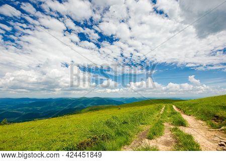 Country Dirt Road Through Grassy Hillside. Mountain Ridge In The Distance Beneath A Gorgeous Cloudsc