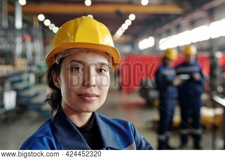 Portrait of content young mixed race woman in yellow hardhat working at factory, she standing in large industrial shop