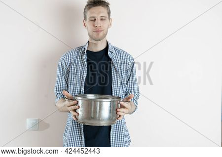 A Young Male Cook Holding A Saucepot With Some Soup Prepared In It, Standing Against The Wall Isolat