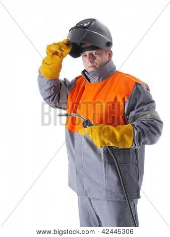Welder wearing protective suit and welding hood holding gas welding gun on white