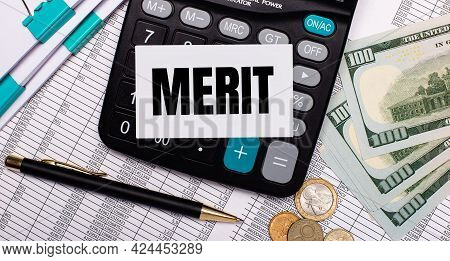 On The Desktop Are Reports, A Pen, Cash, A Calculator And A Card With The Text Merit. Business Conce