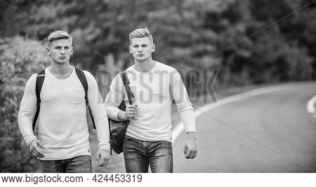 Hiking With Friends Is Cool. Gone To Find Themselves. Travel And Hitch-hiking. Twins Walking Along R