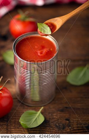 Open Tin Of Tomatoes Sauce With Whole Fresh Tomatoes On A Rustic Wooden Table