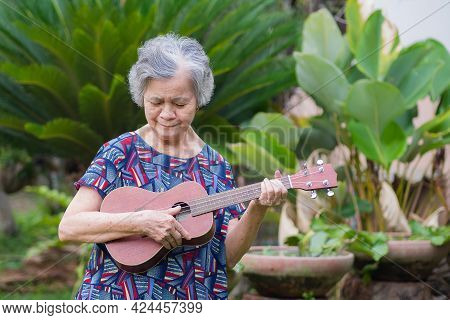 Senior Asian Woman Holding And Looking Ukulele While Standing In A Garden. Relaxing By Singing And P