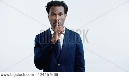 African American Businessman In Suit With Tie Showing Hush Sign Isolated On Blue