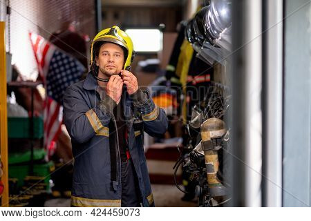 Firefighter Man Set Lock Of Protective Helmet And Look At Camera Also Stay In Room With Accessories
