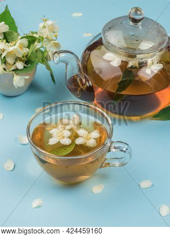 A Cup And A Glass Teapot With Floral Tea On A Blue Background. An Invigorating Drink That Is Good Fo