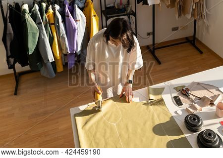 Sewing Process: Woman Tailor Working In Shop With Chalk Patterns On Fabric. Top Angle View Of Young