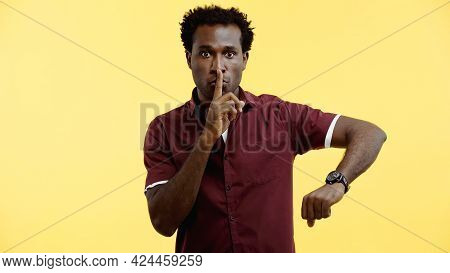 Curly African American Man In Burgundy Shirt And Wristwatch Showing Hush Sign Isolated On Yellow