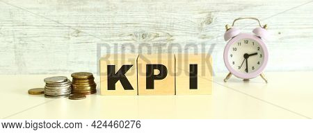 There Are Three Wooden Cubes With Letters On The Table Next To The Coins. The Word Kpi. On A Gray Ba