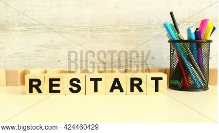 Seven Stacked Wooden Cubes With Letters Restart On A White Work Table On A Gray Background. Business