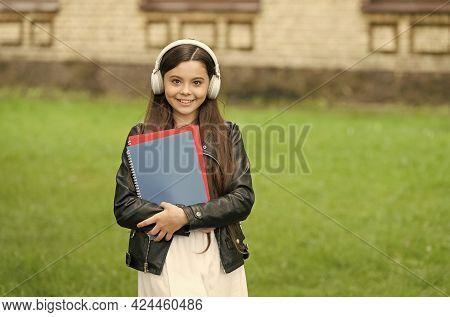Where Knowledge Meets Modern Training Aids. Happy Child Wear Modern Headphones Outdoors. Little Girl