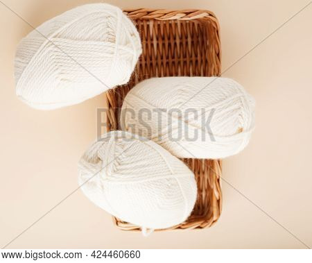 Three White Skeins Of Yarn And A Wicker Basket. Nice Photo For A Hobby, Vertical Orientation. Hobby