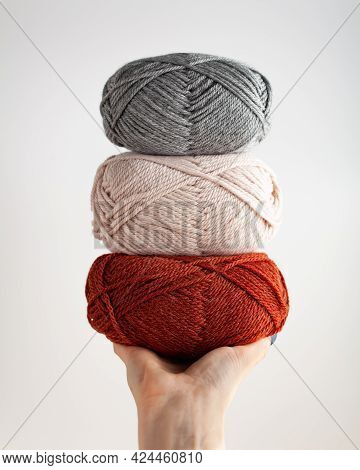 Three Skeins Of Yarn In Hand. Nice Photo For A Hobby, Vertical Orientation. Hobby Aesthetics.