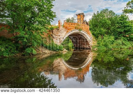 Old Stone Arch Bridge Over River With Reflection In The Water, Summer Day