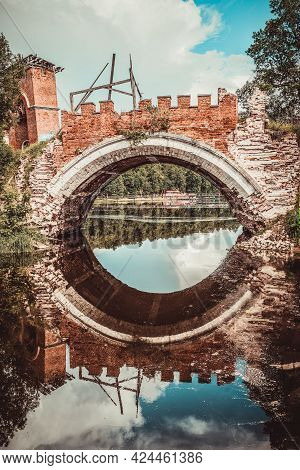 Destroyed Gothic Arch Bridge In An Old Noble Estate With Reflection In The Water.