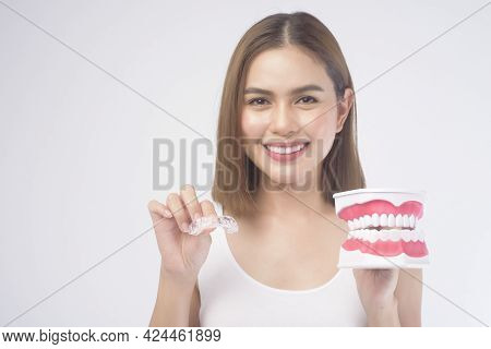 A Young Smiling Woman Holding Invisalign Braces And Artificial Dental Model Over White Background St