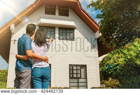 Living Concept And Family Planning : Rear View Asian Couple Were Proud To Look At Their Beautiful Tw