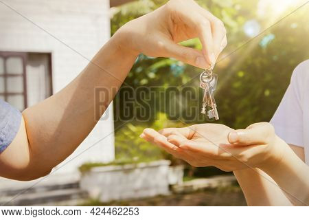 New Home Concept : Handing Over The Key Handed The Two House Keys To The Female Owner Of The New Hom