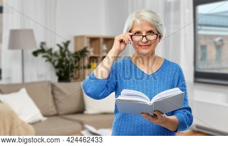 vision, wisdom and old people concept - smiling senior woman in glasses reading book over home living room background
