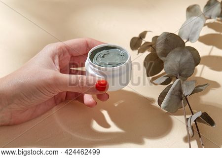 beauty, cosmetics and bodycare concept - hand holding jar of blue cosmetic clay mask over branch of eucalyptus populus on beige background