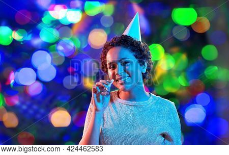 birthday, celebration and nightlife concept - happy smiling young african american woman in party cap with blower in ultraviolet neon lights over bokeh background