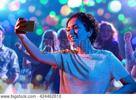 nightlife, technology and people concept - happy young african american woman taking selfie with smartphone in ultraviolet neon lights over nightclub background
