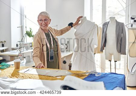 Smiling Mature Fashion Designer Stands Between Mannequin And Cutting Table In Sewing Workshop